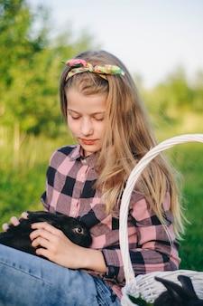 Bella ragazza con un coniglio. la ragazza ride e bacia un coniglio. camicia e jeans. coniglietto di pasqua. ridere forte