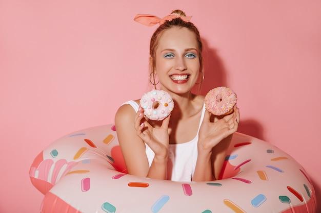 Bella ragazza con orecchini rotondi e trucco alla moda in abiti bianchi che sorride, tiene in mano due ciambelle e posa con un anello da nuoto sul muro rosa