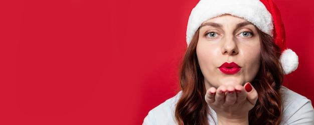 Bella ragazza con cappello santa e avendo i capelli ricci ondulati bruna inviando baci d'aria