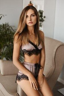 Bella ragazza con un corpo perfetto sexy e capelli biondi lisci in pigiama di seta alla moda all'interno.