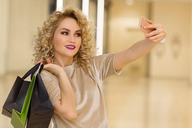 Bella ragazza con le borse della spesa che si fa un selfie con il cellulare.