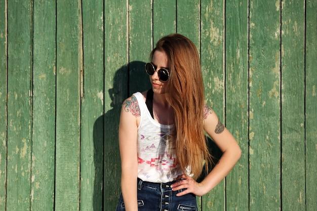 Bella ragazza con il corpo tatuato sulla superficie della parete in legno