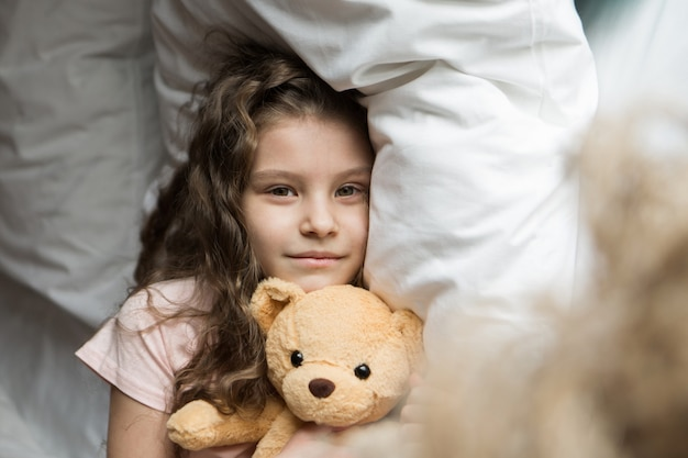 Una bella ragazza con un orsacchiotto un bambino con un giocattolo il concetto di passatempo mattutino dell'infanzia