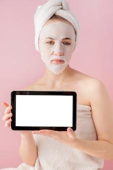 Bella ragazza con una maschera in tessuto e una tavoletta in mano con copia spazio sul rosa