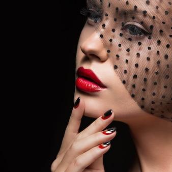 Bella ragazza con un velo, trucco da sera, unghie nere e rosse