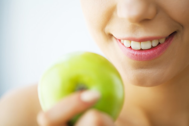 Bella ragazza con i denti bianchi che morde la mela.