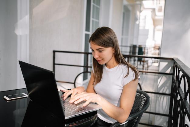 Una bella ragazza lavora con il suo laptop sul balcone in una giornata estiva.
