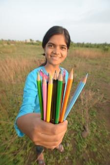 Bella ragazza che scrive e tiene in mano matite colorate all'aperto