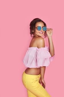 Bella ragazza in jeans gialli e camicia rosa con le mani in alto indossando occhiali da sole in posa ballando sorridente sullo spazio rosa in studio