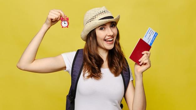 La bella ragazza su giallo esamina la macchina fotografica e tiene un orologio con i biglietti in un passaporto