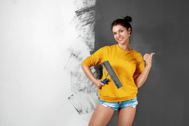 La bella ragazza in un maglione giallo dipinge una parete in vernice grigia. pittura, riparazione, progettazione della stanza. copia spazio.