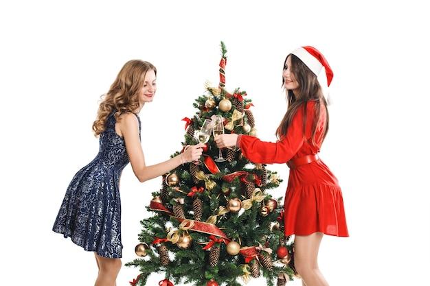 Belle ragazze tintinnano bicchieri intorno all'albero di natale sulla festa di capodanno