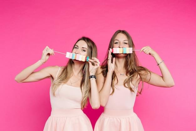 Belle ragazze come bambole si divertono con caramelle marshmallow sul bastone.
