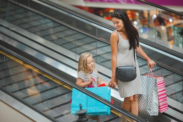 Belle ragazze madre e figlia nel centro commerciale. giovane mamma e il suo piccolo bambino grazioso che comperano insieme. famiglia allegra che compra merci su una vendita
