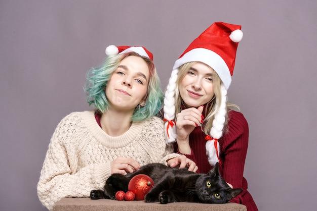 Belle ragazze in maglioni toccano il gatto nero su entrambi i cappelli natale babbo natale giovani donne di ca...