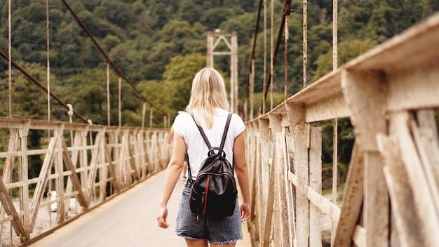 Belle ragazze che viaggiano, camminano su un ponte mentre si godono la splendida vista delle montagne