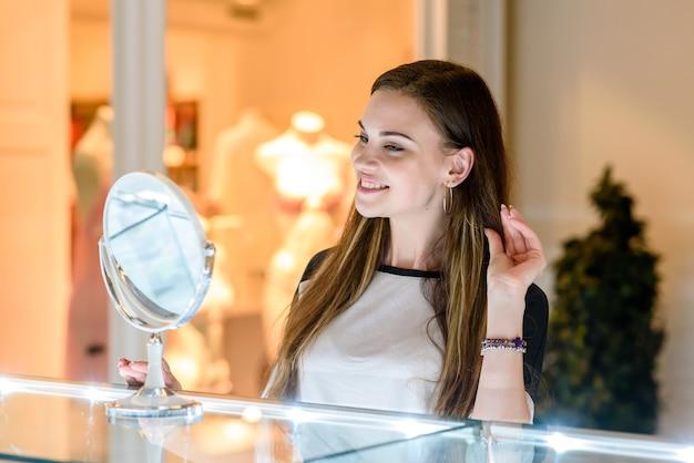 Belle ragazze provano orecchini al centro commerciale.