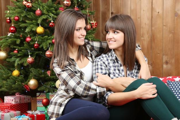 Belle ragazze gemelle vicino all'albero di natale a casa