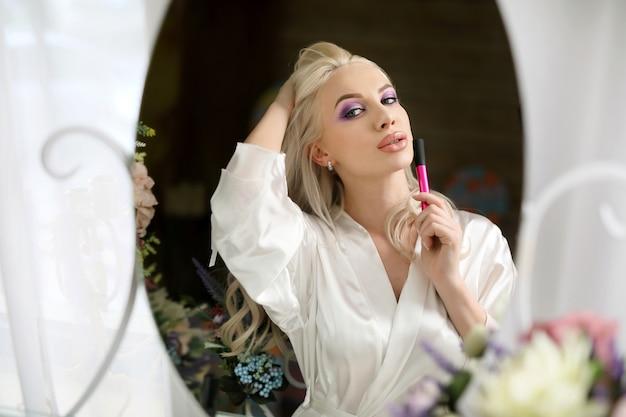 Bella ragazza affascinante in bianco, con il trucco si guarda allo specchio.