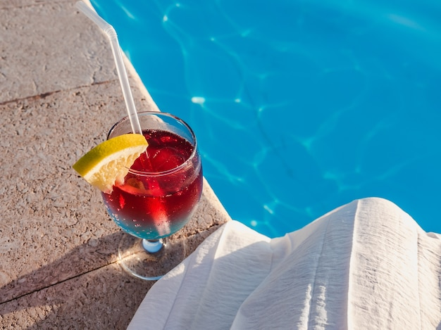 Bellissimo bicchiere con un cocktail a bordo piscina. vista dall'alto, primo piano. concetto di tempo libero e viaggi