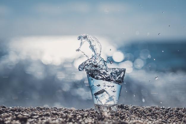Bellissimo bicchiere con ghiaccio e acqua minerale pura in riva al mare.