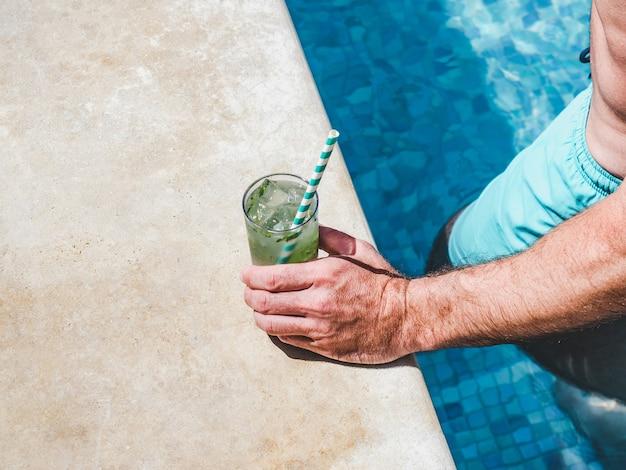 Bellissimo bicchiere con un cocktail rinfrescante e un uomo attraente