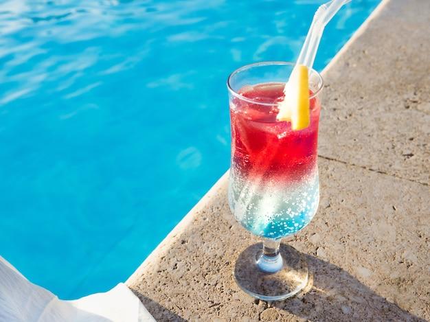 Bellissimo bicchiere con un rinfrescante cocktail sullo sfondo della piscina