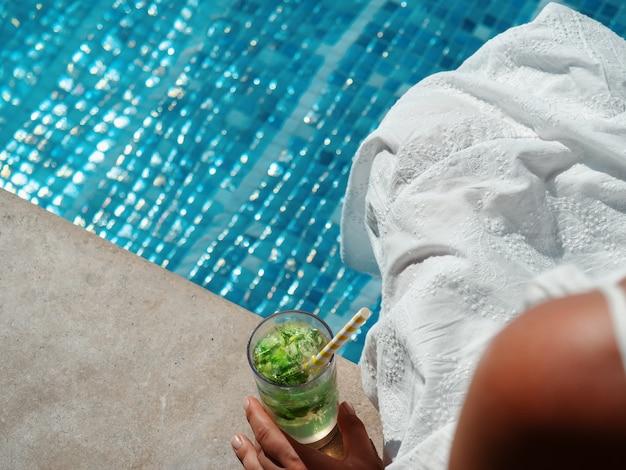 Bellissimo bicchiere con un cocktail rinfrescante e una bella donna