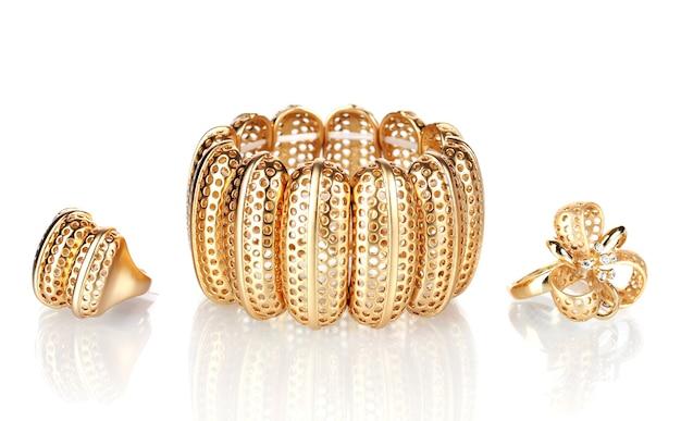 Bellissimo braccialetto d'oro e anelli isolati su bianco