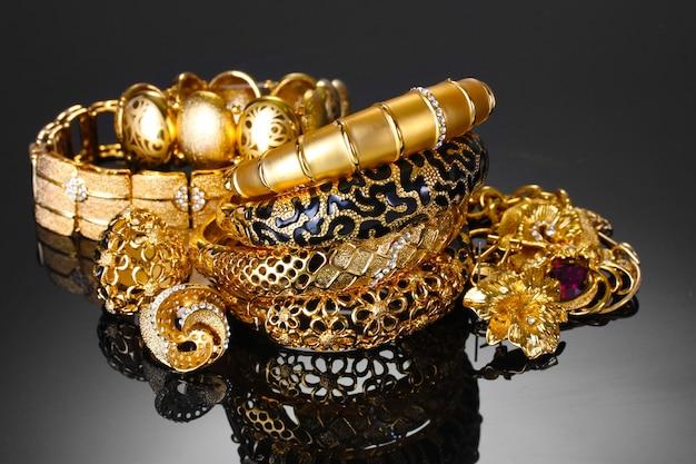 Bellissimi braccialetti d'oro, anelli e gioielli su sfondo grigio