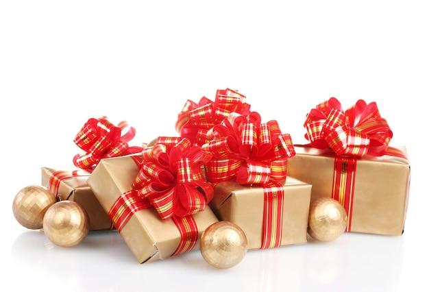 Bellissimi regali dorati con nastro rosso e palle di natale isolate su bianco