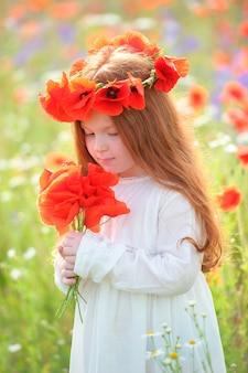 Bella ragazza dai capelli d'oro in un abito bianco e un mazzo di fiori di campo