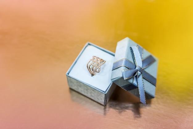Bellissimi gioielli d'oro in confezione regalo su sfondo dorato