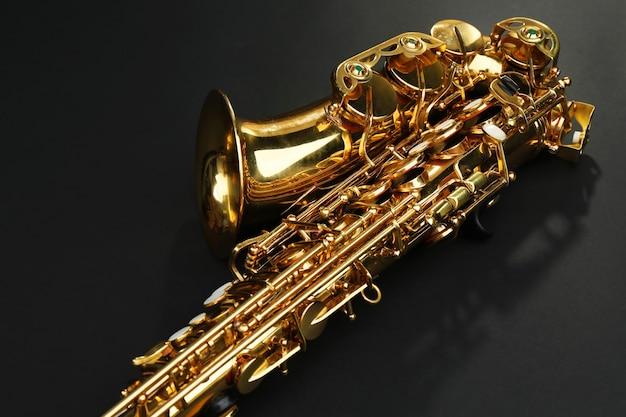 Bello sassofono dorato sulla tavola nera, fine in su