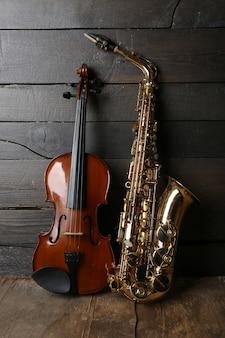 Bellissimo sassofono dorato con violino su tavola di legno