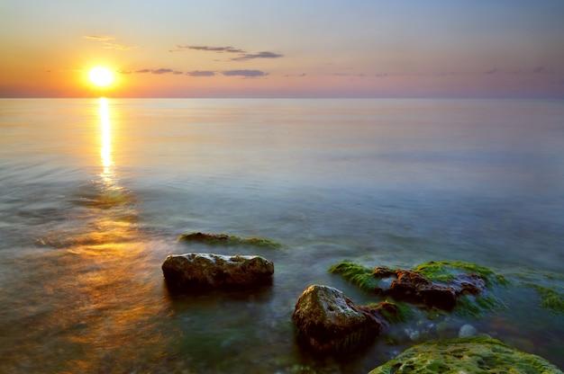 Bellissimo tramonto dorato sulla costa rocciosa del mar nero in crimea il giorno d'estate.