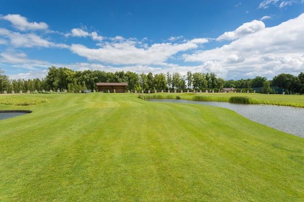 Bellissimo campo da golf con erba verde perfetta e ostacoli d'acqua in una luminosa giornata di sole