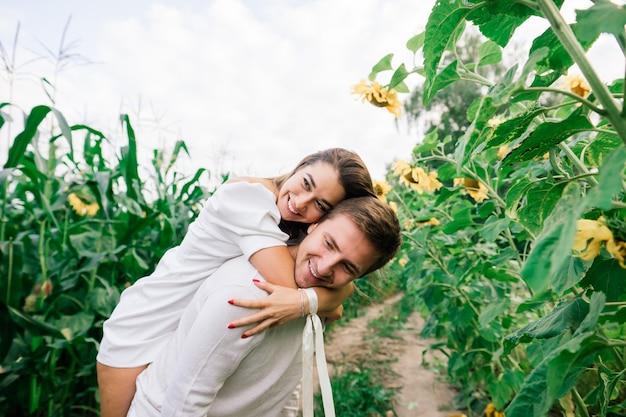 Bella donna splendida ed elegante bel maschio, coppia rustica in un campo di girasoli baciare, tenero
