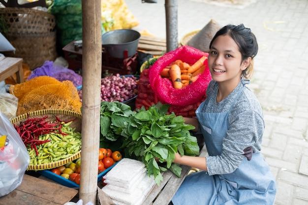 La bella donna del fruttivendolo organizza gli spinaci per la sua esposizione della bancarella di verdure in un mercato tradizionale