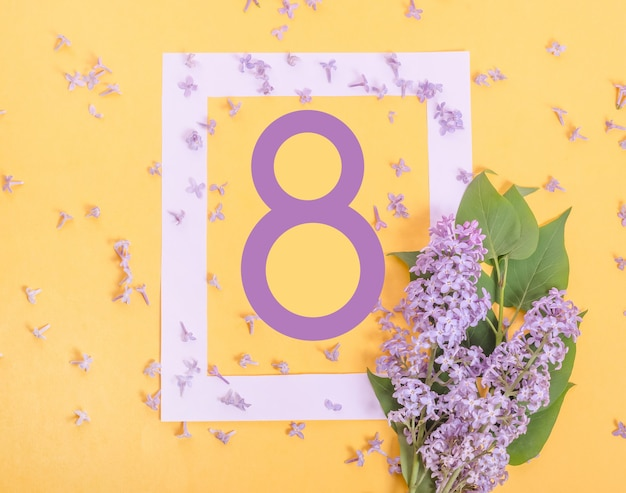 Bellissimo biglietto di auguri per l'8 marzo con fiori lilla su un muro giallo, giornata internazionale della donna