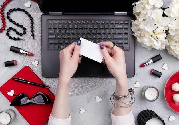Le mani della bella donna governata che tengono la cartolina d'auguri di affari sulla tavola del ministero degli interni