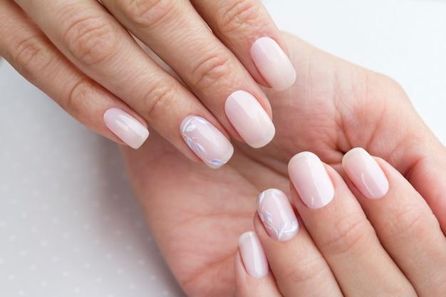 Mani di bella donna curata con unghie femminili sul tavolo grigio chiaro.