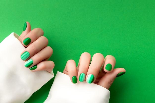 Le mani della bella donna curata con le unghie verdi progettano sulla superficie verde