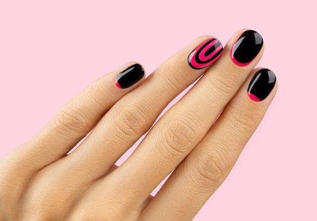 Bella mano della donna curata con manicure alla moda sul rosa
