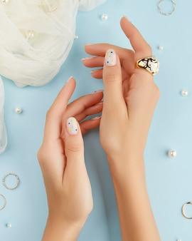 Le belle mani della donna curata con il design delle unghie estive su sfondo blu