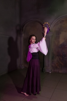 Bella donna zingara primo piano nella stanza buia della chiesa cattedrale con tamburello musicale in mano