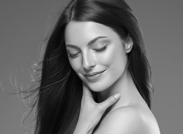 La pelle di beuty dei capelli lunghi del brunette della bella donna dei capelli compone. colpo dello studio. monocromo. grigio. bianco e nero.