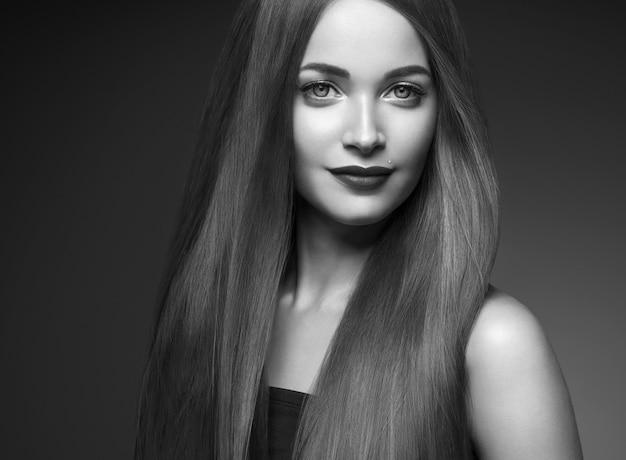 Bella donna capelli lunghi lisci bruna acconciatura bellezza capelli sani modello femminile ritratto. colpo dello studio. monocromo. grigio. bianco e nero.