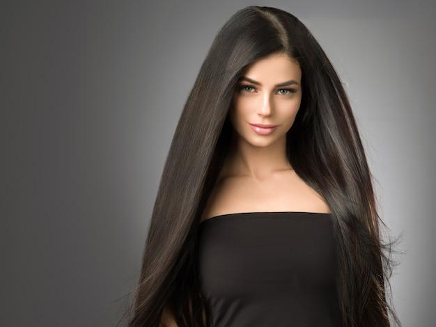 Bella donna dei capelli con il ritratto femminile dell'acconciatura di helathy di bellezza lunga del brunette. colpo dello studio.