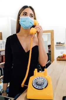 Bellissima receptionist del parrucchiere che prende in mano un vecchio telefono giallo con una maschera per il viso a causa del coronavirus